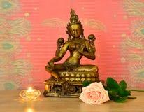 Estatua, vela y una rosa Imagenes de archivo