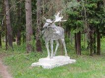 Estatua vieja de un alce con las astas en el bosque fotos de archivo