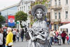 Estatua viva en un sombrero en el fondo de la población, de los edificios y de la bandera de Croacia en el celebrat imagenes de archivo