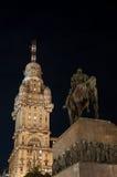 Estatua y rascacielos públicos en la noche Imagen de archivo