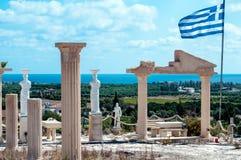 Estatuas antiguas con la bandera griega Imagen de archivo libre de regalías