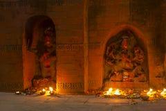 Estatuas antiguas de deidades en la pared con las velas ardientes en la noche imagen de archivo libre de regalías