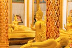 Estatuas antiguas de oro de Buda en diversas actitudes en templo Imagen de archivo