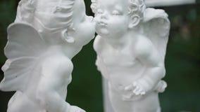 Estatuas blancas de dos ángeles que se besan La cámara se mueve de abajo hacia arriba metrajes