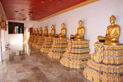 Estatuas budistas de oro en pedestales coloreados Foto de archivo libre de regalías