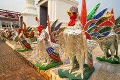 Estatuas coloridas del gallo delante del tubo principal en un templo budista en Tailandia fotografía de archivo
