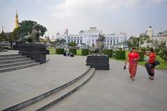Estatuas de Chinthe en Rangún Myanmar con las mujeres hermosas en rojo en frente y templo y edificios coloniales en el fondo fotos de archivo libres de regalías
