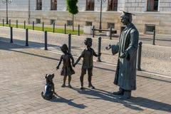 Estatuas de los niños que juegan con su profesor imagen de archivo