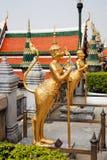 Estatuas de oro de un kinnara en Wat Phra Kaew, Bangkok foto de archivo