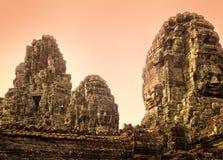 Estatuas de piedra de Buddhas sonriente en el complejo de Angkor Thom, Siem Reap, Camboya en la salida del sol imágenes de archivo libres de regalías