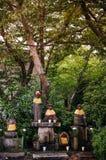 Estatuas de piedra del monje de Jizo Bosatsu con el babero y el sombrero debajo del árbol en g fotografía de archivo libre de regalías
