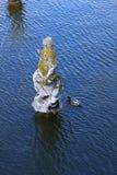 Estatuas de piedra en la charca del jardín fotos de archivo