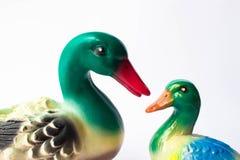 Estatueta cerâmica de um pato em um fundo branco com as penas brilhantemente coloridas Patinho com pato da mãe ilustração royalty free