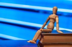 A estatueta de madeira do manequim, do manequim ou do homem senta-se sobre Fotografia de Stock