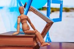 A estatueta de madeira do manequim, do manequim ou do homem senta-se sobre Imagem de Stock Royalty Free