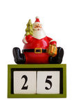 Estatueta de Papai Noel que senta-se nos cubos que mostram a data 25 isolada no fundo branco Imagem de Stock Royalty Free