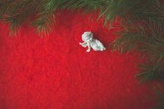 Estatueta do anjo que senta-se no seixo derramado e no pano de lã vermelho imagens de stock