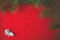 Estatueta do anjo que senta-se no seixo derramado e no pano de lã vermelho fotografia de stock
