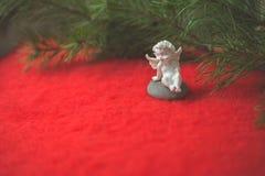 Estatueta do anjo que senta-se no seixo derramado e no pano de lã vermelho foto de stock royalty free