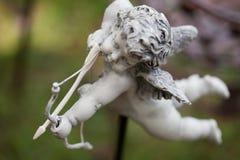 Estatueta do cupido que dispara em uma seta Foto de Stock
