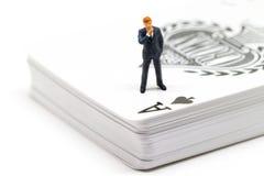 Estatueta do homem e mesa de pensamento do cartão de jogo Micro modelo do homem no terno que está no trunfo Fotografia de Stock