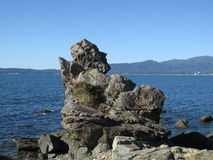 A estatueta gosta da pedra em uma costa rochosa japonesa fotografia de stock royalty free
