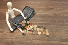 Estatueta humana de madeira, carteira preta vazia e moedas inglesas, Ove Fotos de Stock Royalty Free