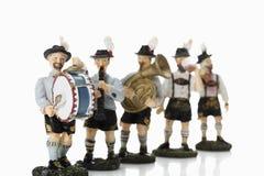 Estatuetas bávaras que jogam a música no fundo branco fotografia de stock