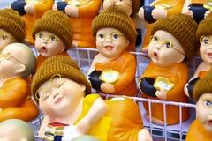 Estatuetas bonitos da monge budista com espetáculos e os chapéus felpudos imagens de stock royalty free