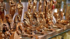 Estatuetas de gatos egípcios da pedra e dos outros produtos em prateleiras de loja em Egito filme