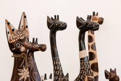 Estatuetas de madeira sob a forma dos girafas e dos gatos fotografia de stock royalty free