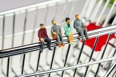 estatuetas diminutas que sentam-se na borda do carrinho de compras do cromo Fotos de Stock Royalty Free