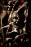 Estatuetas do negro cortadas do ébano em um fundo vermelho fotografia de stock