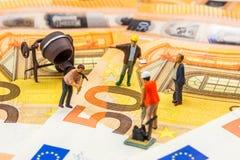 Estatuetas pequenas que trabalham duramente em 50 euro- cédulas novas Fotografia de Stock