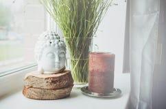 Estatuilla blanca de la cabeza de Buda en soporte de madera con la vela marrón grande un alféizar, fondo floral verde de la plant Foto de archivo