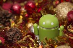Estatuilla de Android con la guirnalda de la Navidad Fotografía de archivo libre de regalías