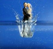 Estatuilla de la boda que cae abajo al agua azul Imágenes de archivo libres de regalías