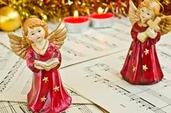 Estatuilla de la Navidad de ángeles en una hoja de música Imágenes de archivo libres de regalías