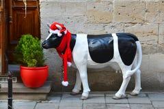 Estatuilla de la Navidad de una vaca manchada en un sombrero rojo y una bufanda roja Imagen de archivo libre de regalías