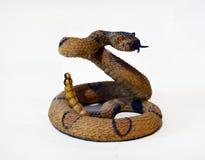 Estatuilla de la serpiente de cascabel en el fondo aislado blanco foto de archivo