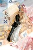 Estatuilla de los pares de la boda sobre notas euro Fotografía de archivo libre de regalías