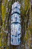 Estatuilla de madera pegada en un árbol Fotografía de archivo