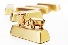Estatuilla de oro del oso del toro en barras de oro foto de archivo