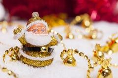 Estatuilla de Papá Noel y alarmas de oro Fotografía de archivo