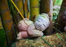 Estatuilla de piedra en un fondo de bambú Fotos de archivo libres de regalías