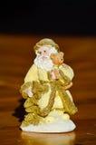 Estatuilla de Santa Claus sonriente de oro que sostiene un poco oso Imagen de archivo libre de regalías
