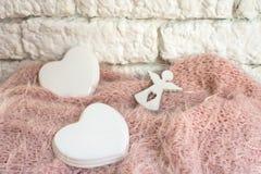 Estatuilla del ángel con un corazón de la porcelana en una manta rosada en una pared ligera foto de archivo libre de regalías
