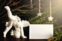 Estatuilla del ángel, estrellas de la Navidad y tarjeta de Navidad en blanco Fotos de archivo