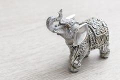Estatuilla del elefante indio en la tabla de madera Fotos de archivo