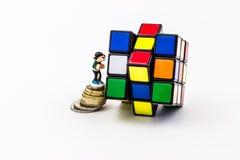 Estatuilla en las monedas que suben en el cubo del rubik Foto de archivo libre de regalías